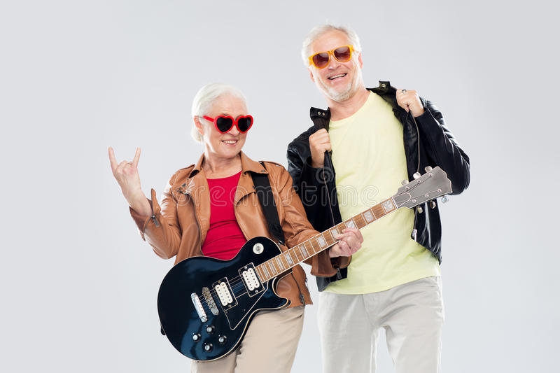 Senior couple with guitar showing rock hand sign royalty free stock images