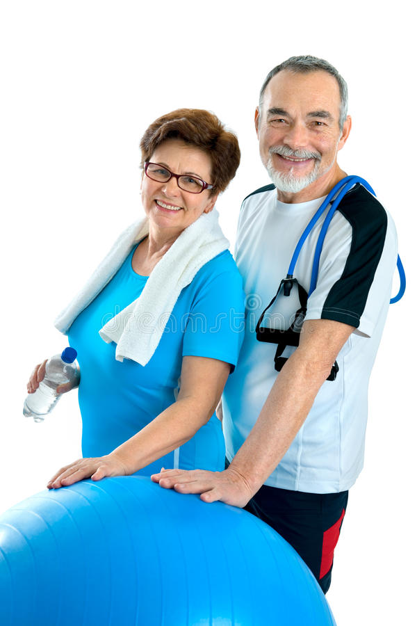 Senior couple in gym. Smiling elderly couple working out in gym. Isolated on white stock images