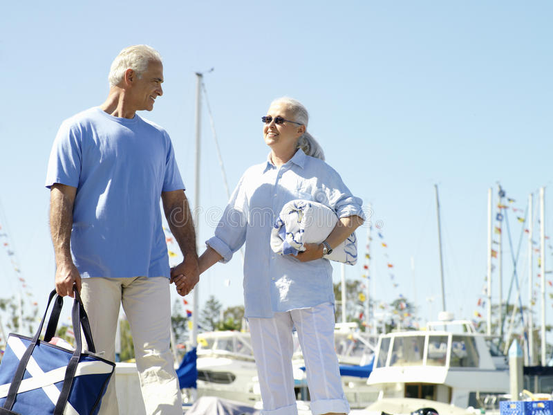 Senior couple hand in hand on jetty, smiling at each other, low angle view stock images