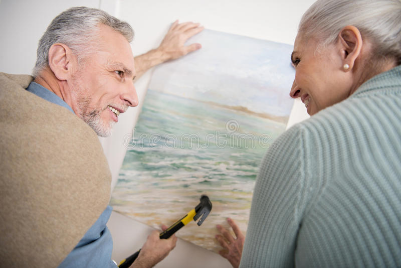 Senior couple hanging together picture on wall at new home royalty free stock image