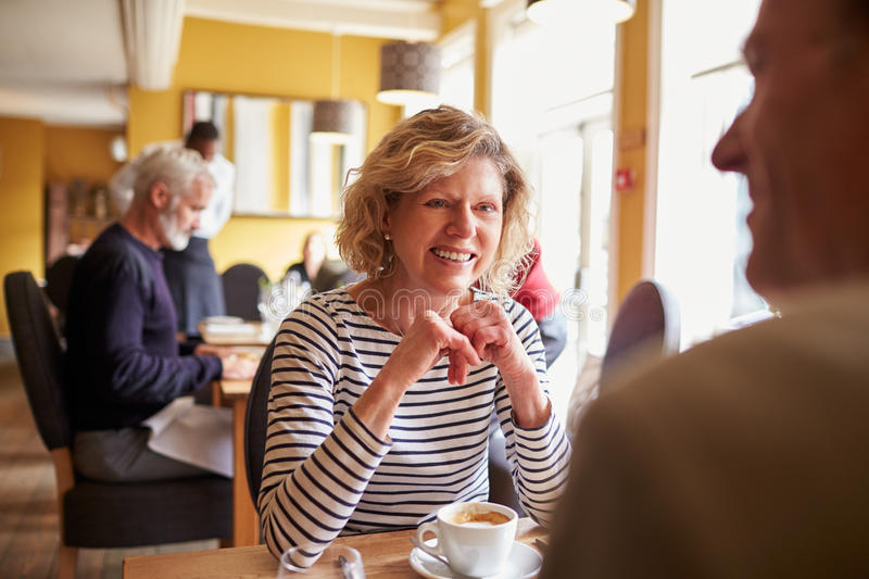 Senior couple have coffee at restaurant, over shoulder view royalty free stock photography
