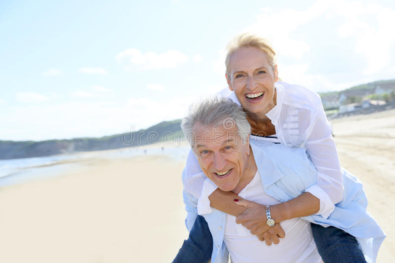 Senior couple having fun on the beach royalty free stock images