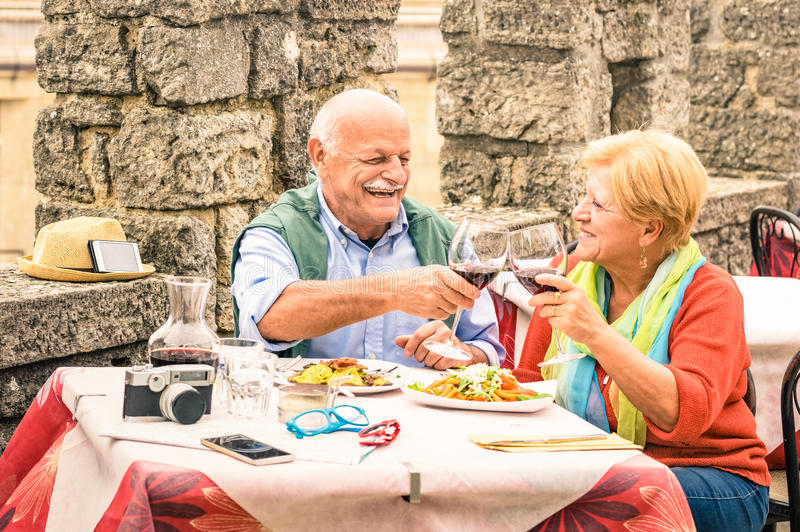 Senior couple having fun and eating at restaurant during travel. Mature men and women wife in old city town bar during active elderly vacation royalty free stock photo