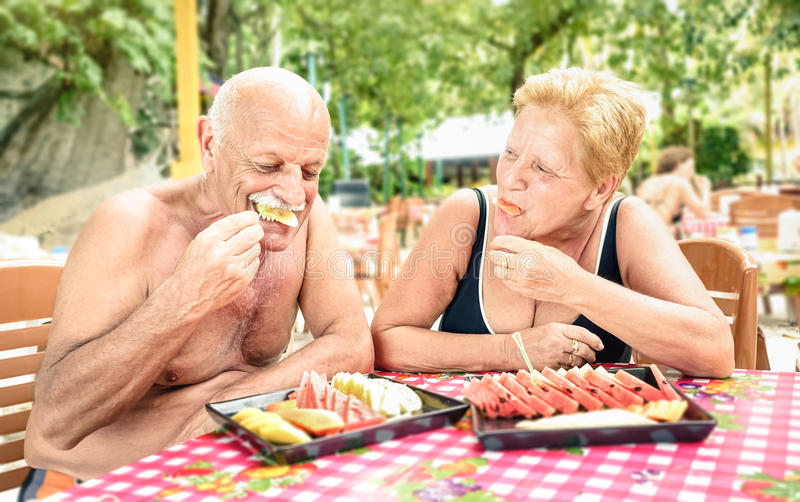 Senior couple having fun eating season fruit in thai restaurant royalty free stock photography