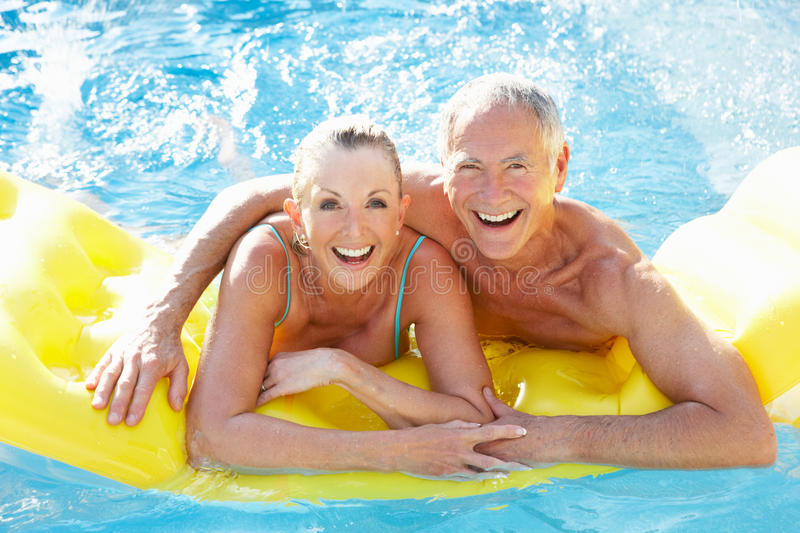 Senior couple having fun in pool royalty free stock images