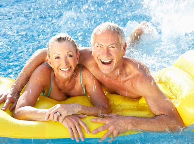 Senior couple having fun in pool stock photography