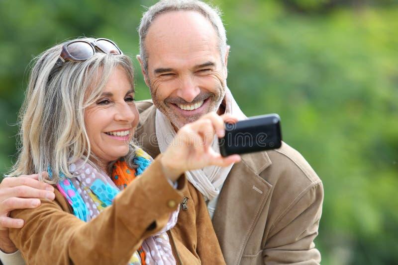 Senior couple having fun taking picture royalty free stock image