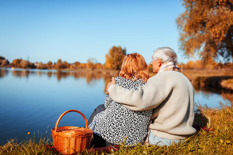 Senior couple having picnic by autumn lake. Happy man and woman enjoying nature and hugging. Romantic date royalty free stock image