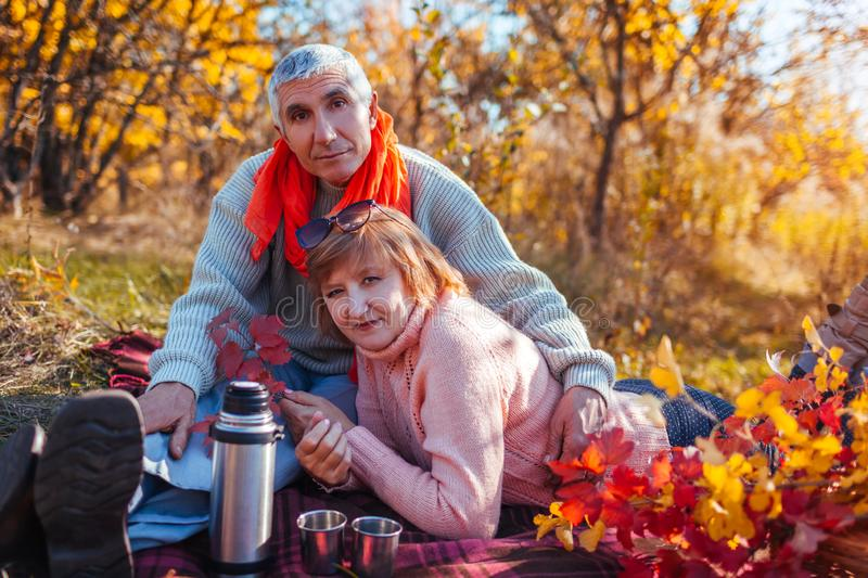 Senior couple having tea in autumn forest. Happy man and woman enjoying picnic and nature royalty free stock photography