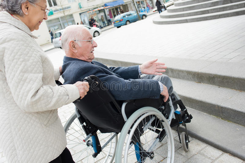 Senior couple having trouble moving disabled husband through city stock images