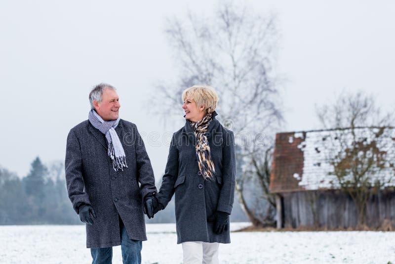 Senior couple having walk in winter royalty free stock photos