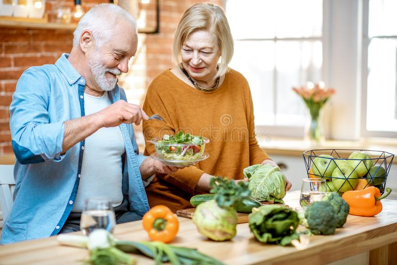 Senior couple with healthy food at home. Cheerful senior couple eating salad standing together with healthy food on the kitchen at home. Concept of healthy stock photo