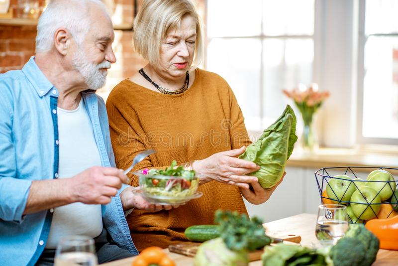 Senior couple with healthy food at home. Cheerful senior couple eating salad standing together with healthy food on the kitchen at home. Concept of healthy stock photography