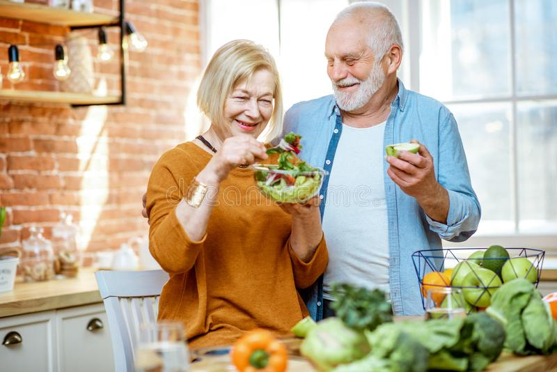 Senior couple with healthy food at home. Portrait of a cheerful senior couple with salad and healthy food on the kitchen at home. Concept of healthy nutrition in stock images