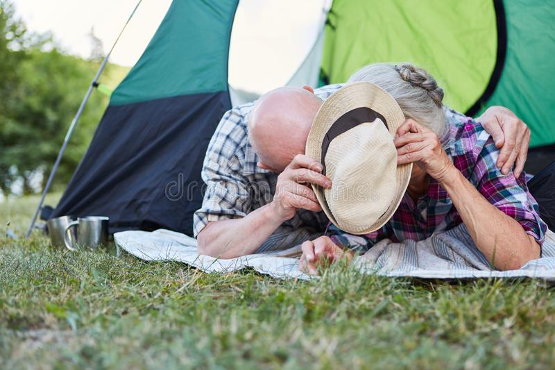Senior couple hiding behind a hat. Silly senior couple in tent is hiding behind a hat at the campsite royalty free stock photo