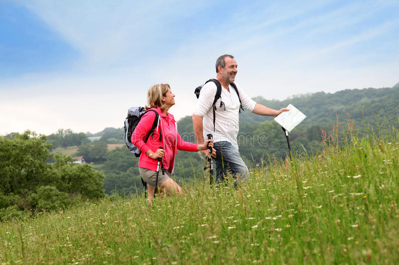 Senior couple hiking in meadow royalty free stock image