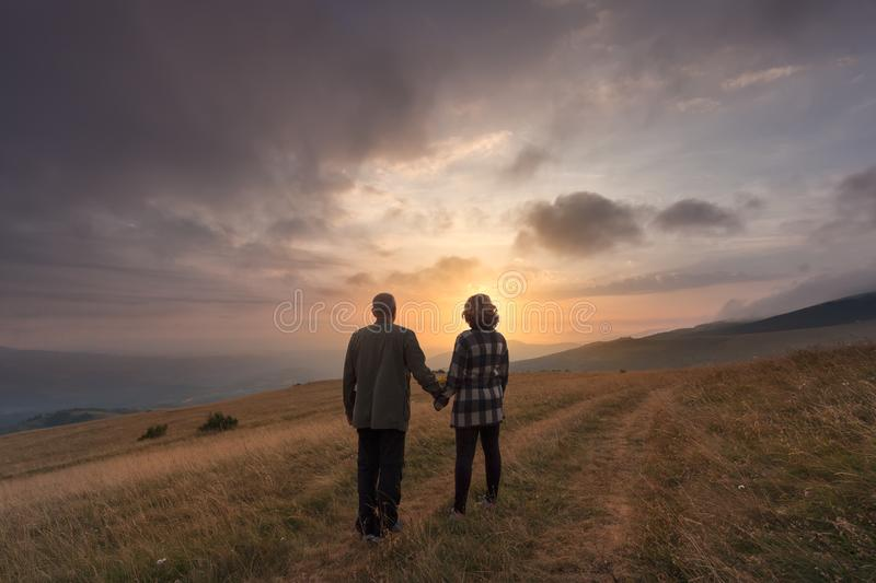 Senior couple hold hands on hill at idyllic sunset stock photography