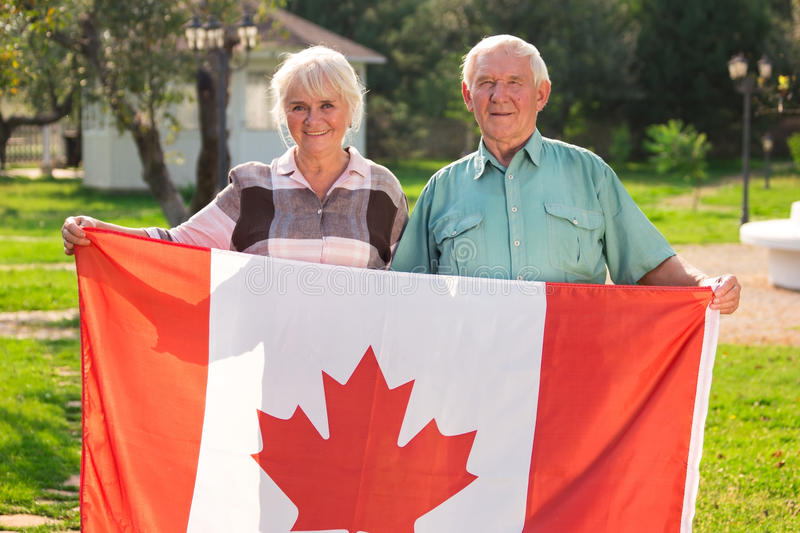 Senior couple holding Canadian flag. Man and women outdoors. Life in Canada royalty free stock photography