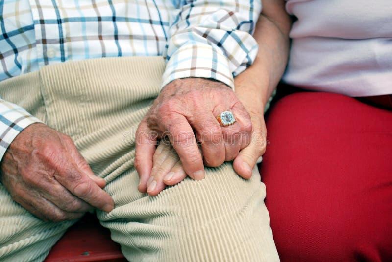 Senior couple holding hands royalty free stock photo