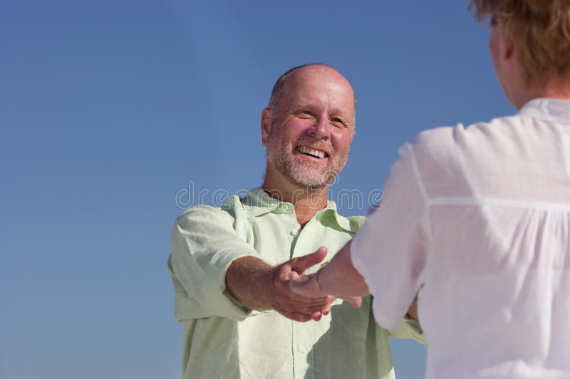 Senior couple holding hands on beach, smiling at each other, low angle view stock image