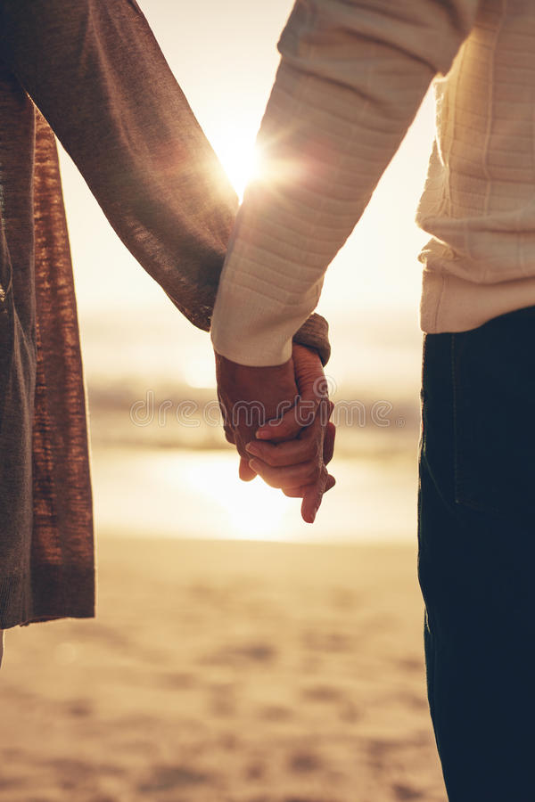 Senior couple holding hands on the beach at sunset royalty free stock image