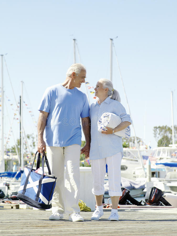 Senior couple holding hands on jetty, smiling at each other, low angle view stock image