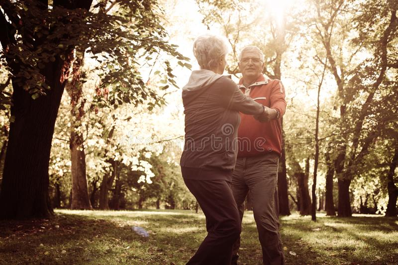 Senior couple holding hands and rotate in circle. royalty free stock image