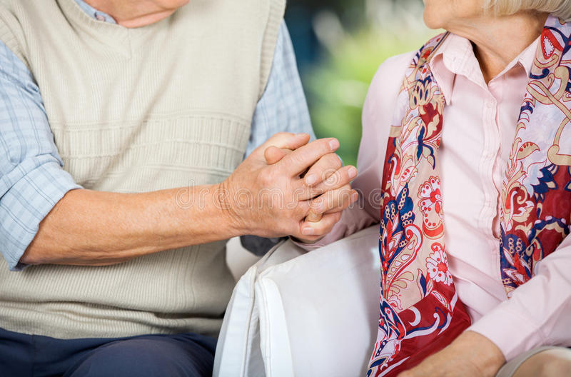 Senior Couple Holding Hands While Sitting On royalty free stock photos