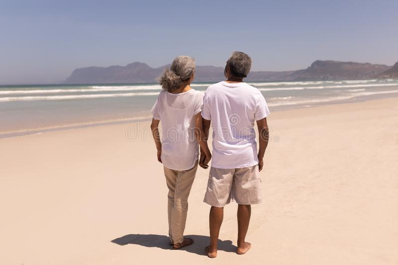 Senior couple holding hands and walking on beach with mountains in the background stock image