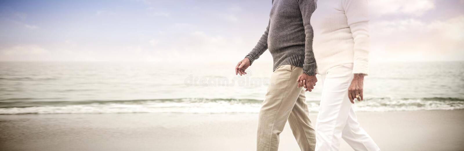 Senior couple holding hands and walking on the beach stock image