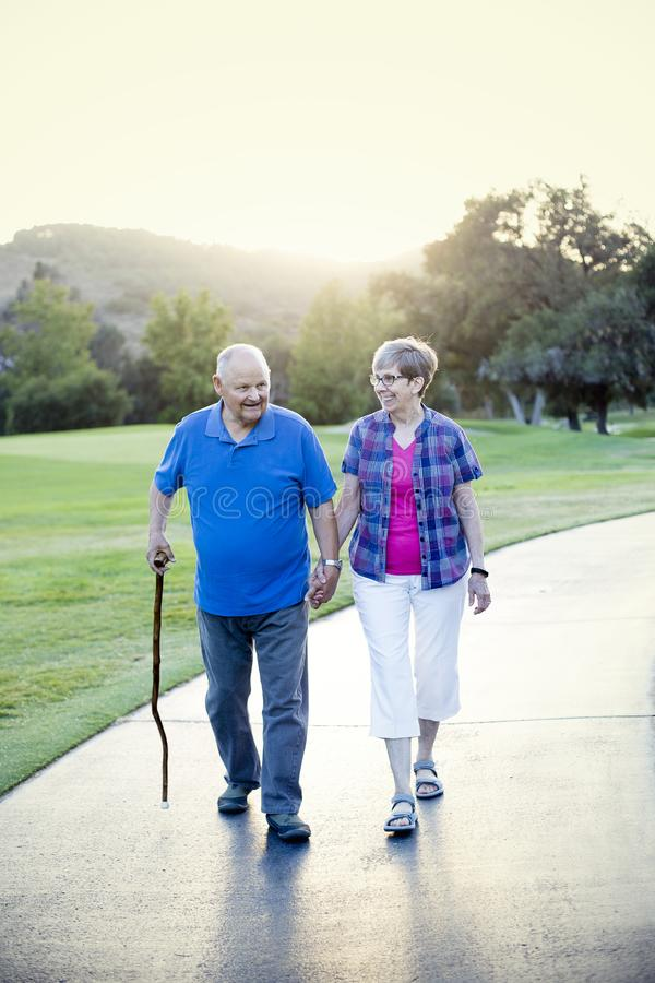 Senior couple holding hands and walking together outdoors on a sunny day royalty free stock image