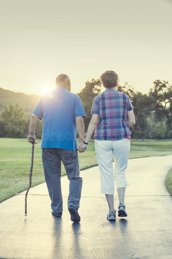Senior couple holding hands and walking together outdoors into the sunset royalty free stock image