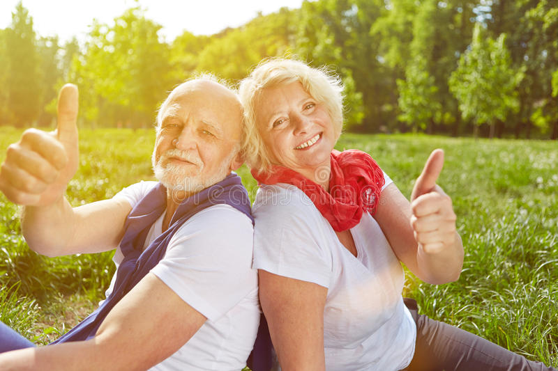 Senior couple holding thumbs up in summer vacation stock images