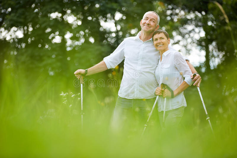 Senior couple on holiday doing nordic walking stock photos