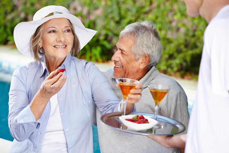 Senior couple in holiday drinking cocktails royalty free stock photography