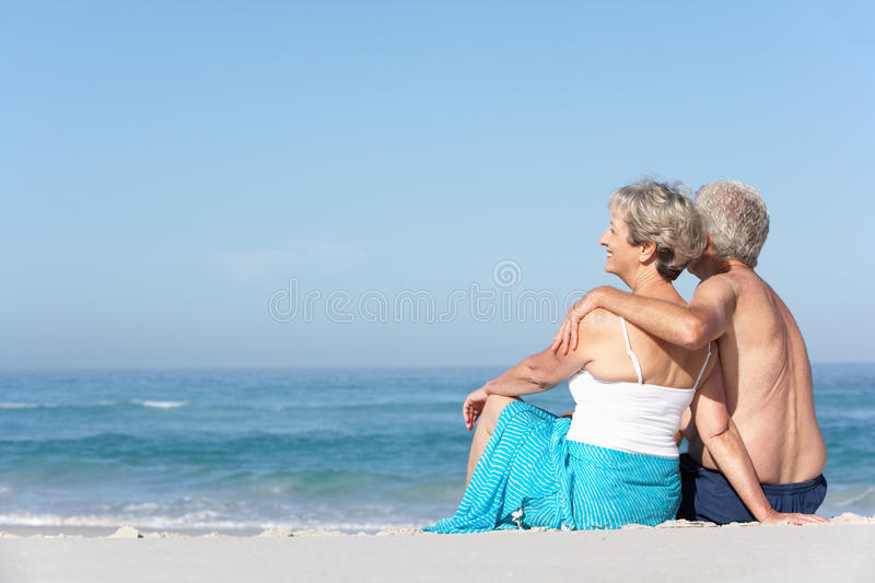 Download Senior Couple On Holiday Sitting On Sandy Beach Stock Photo - Image of female, affectionate: 14689902
