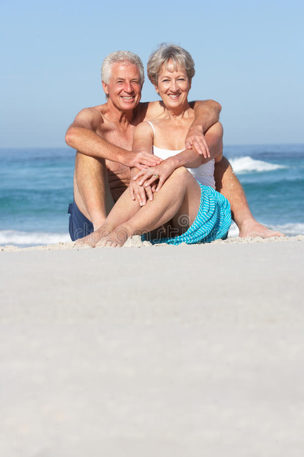 Download Senior Couple On Holiday Sitting On Sandy Beach Stock Image - Image of beach, shore: 14689993