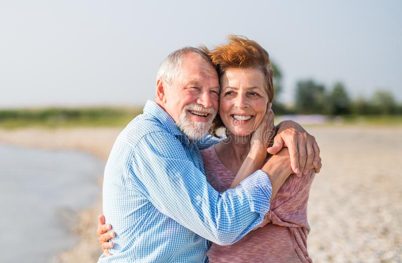 Senior couple on a holiday on a walk by the lake, hugging. Front view of senior couple on a holiday on a walk by the lake, hugging stock photos