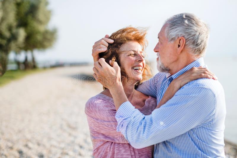 Senior couple on a holiday on a walk by the lake, hugging. royalty free stock photo