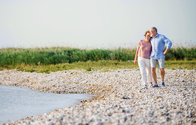 Senior couple on a holiday walking by the lake. Copy space. A senior couple on a holiday walking by the lake. Copy space stock images