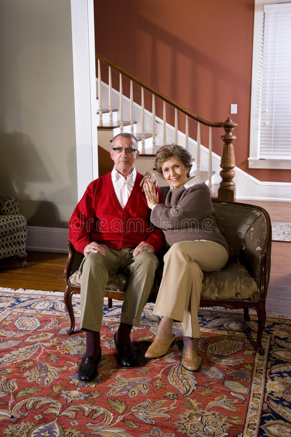 Senior couple at home in living room on sofa. Portrait of senior couple at home in living room sitting on sofa stock image