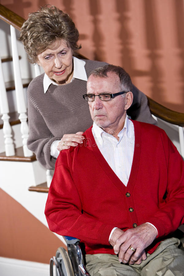 Senior couple at home, man in wheelchair. Serious senior couple at home, man in wheelchair royalty free stock photo
