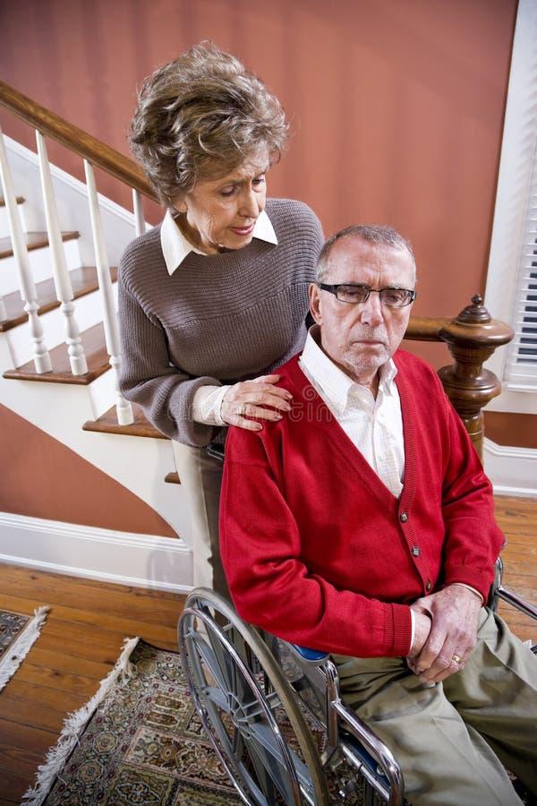 Senior couple at home, man in wheelchair
