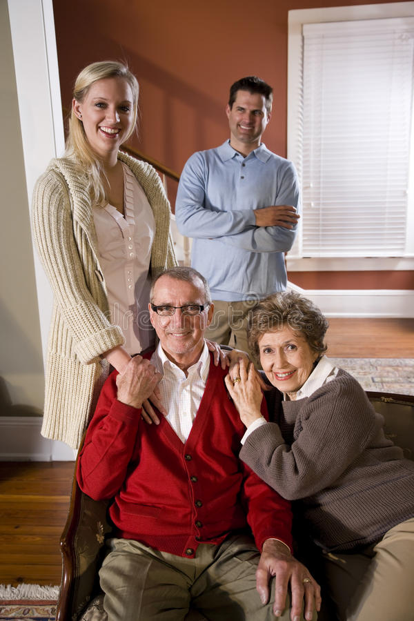 Senior couple at home on sofa with adult children stock photography