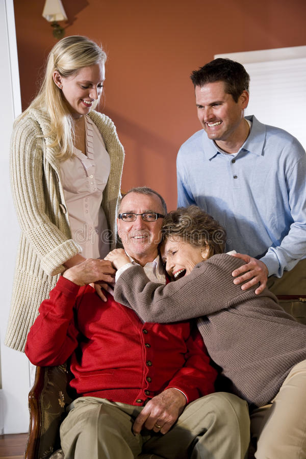 Senior couple at home on sofa with adult children. Portrait of senior couple at home on sofa with adult children royalty free stock photo