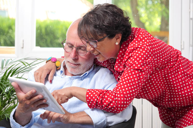 Senior couple at home using digital tablet royalty free stock photo