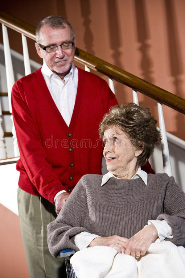 Senior couple at home, woman in wheelchair. Smiling senior couple at home, woman in wheelchair royalty free stock image