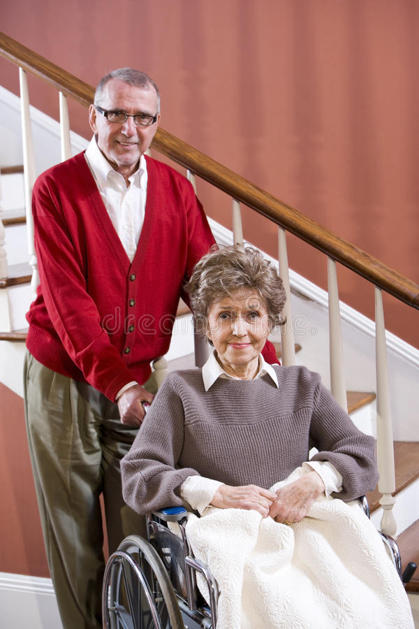 Senior couple at home, woman in wheelchair. Senior couple at home, woman in 70s in wheelchair royalty free stock photo