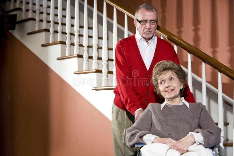Senior couple at home, woman in wheelchair. Smiling senior couple at home, woman in wheelchair stock photos
