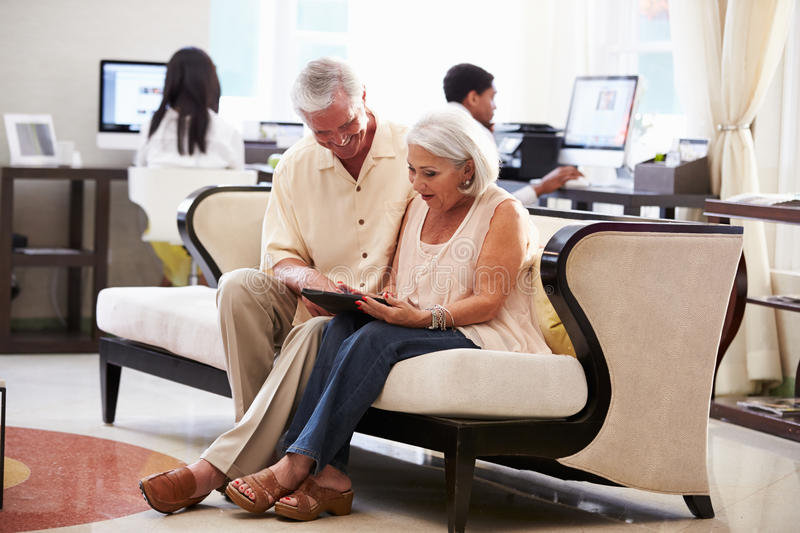 Senior Couple In Hotel Lobby Looking At Digital Tablet stock photos
